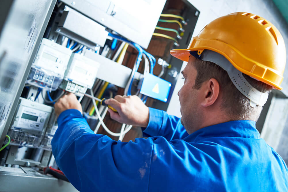 Electrician working on a panel with blue suit and yellow hard hat